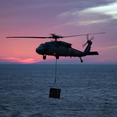 """A U.S. Navy MH-60 Knighthawk attached to the """"Chargers"""" of Helicopter Sea Combat Squadron 26 prepares to drop supplies onto the flight deck of the Nimitz Class Aircraft Carrier USS THEODORE ROOSEVELT (CVN 71). Helicopter Sea Combat Squadron 26 transferred supplies from the Military Sealift Command Military Sealift Command Advanced Auxiliary Dry Cargo/ Ship USNS LEWIS AND CLARK (T-AKE 1) in the Atlantic Ocean, Dec. 15. 2006. (U.S. Navy photo by Mass Communication Specialist 1st Class John Mason) (Released)"""
